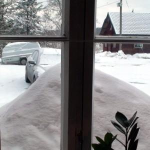 Iso lumikasa keittiön ikkunan edessä